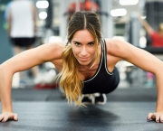 Young beautiful woman doing pushups in the gym. Girl wearing sportwears clothes.