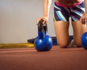 Fitness woman doing push ups with kettlebells